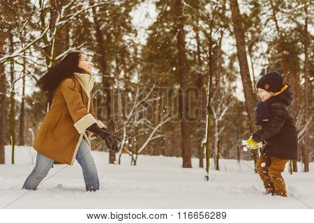 Happy family in warm clothing. Smiling mother and son play snowballs outdoor. The concept of winter