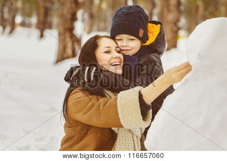 Happy family in warm clothing. Smiling mother and son making a snowman outdoor. The concept of winte
