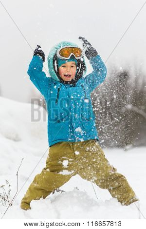 Happy baby boy playing snow in winter day