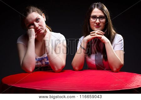 Two young woman and red table