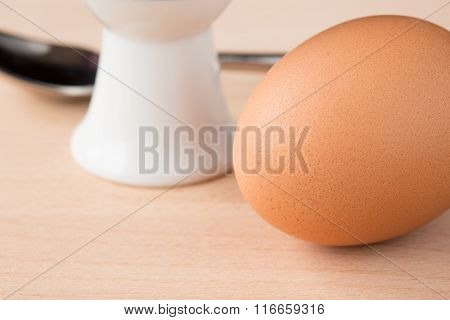 Single brown egg with eggcup and spoon