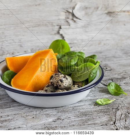 Pumpkin, Quail Eggs, Spinach In The Enameled Bowl - Raw Ingredients For Cooking, On A Light Rustic W