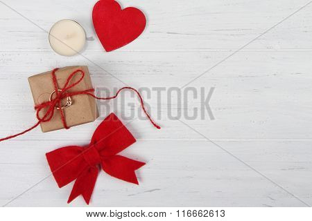 Gift box, heart and bow on white wooden background