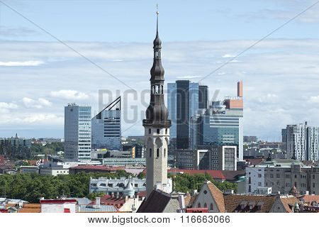 The old spire of the medieval town hall on the background of the modern city. Tallinn, Estonia