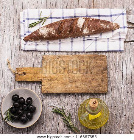 Simple kitchen still life of fresh dark-grain bread, a jug olive oil