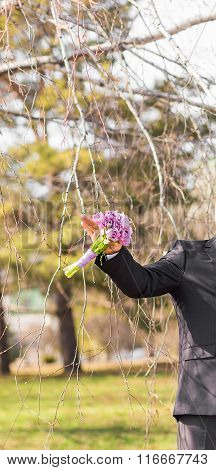 spring bouquet in the hands of the groom