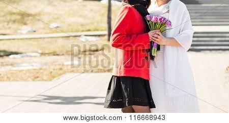 bride and bridesmaid outside happy hug