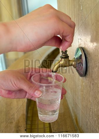 Man pours water on the mineral springs in a plastic cup