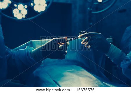 Close-up of gloved hands holding surgical scissors