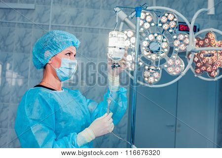 Nurse adjusting infusion bottle with against background of the o