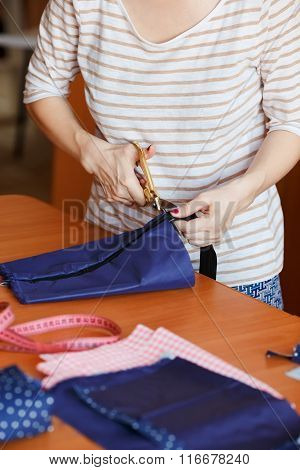 Young Woman Sewing At Home, Hemming Blue Fabric. Fashion Designer Creating New Fashionable Styles.