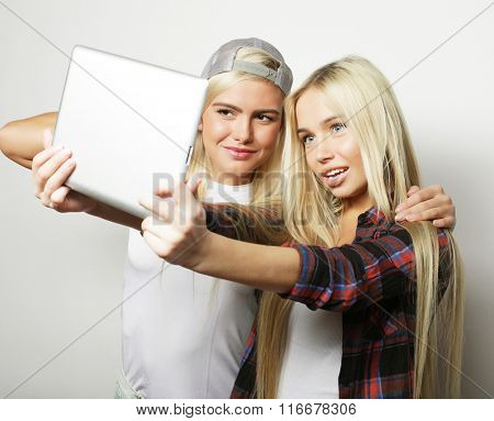 two hipster girls friends taking selfie with digital tablet