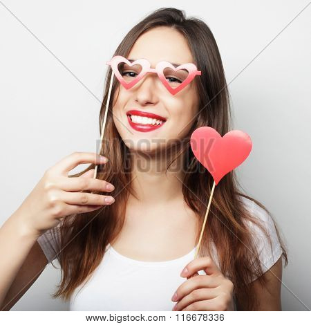 Playful young woman holding a party heart.
