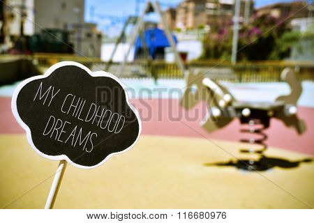 a chalkboard in the shape of a thought bubble with the text my childhood dreams in a public urban playground with a spring rider in the background, with a vignette added