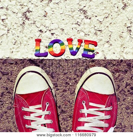 closeup of the feet of a man wearing red sneakers stepping on the asphalt where a pile of letters painted as the rainbow flag form the word love