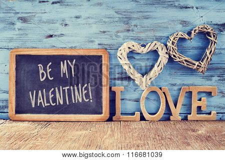 a chalkboard with the text be my valentine, two heart-shaped ornaments made with natural fibers and some wooden letters forming the word love, against a blue rustic wooden background