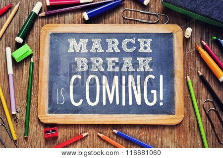 high-angle shot of a rustic wooden table with some pencils and markers and a chalkboard with the text march break is coming written in it