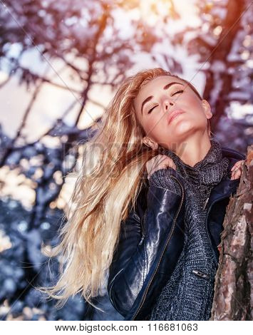Portrait of gentle sexy blond woman with closed eyes near tree, gorgeous fashion model posing in winter park