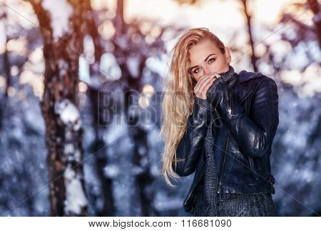 Portrait of cute blond female wearing stylish leather jacket in winter park, warming up her arms, wintertime fashion