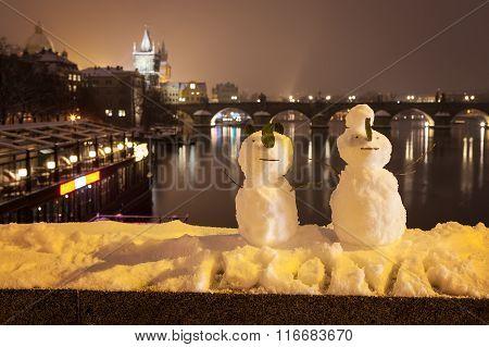 Snowmans and Charles Bridge as background, Czech Republic