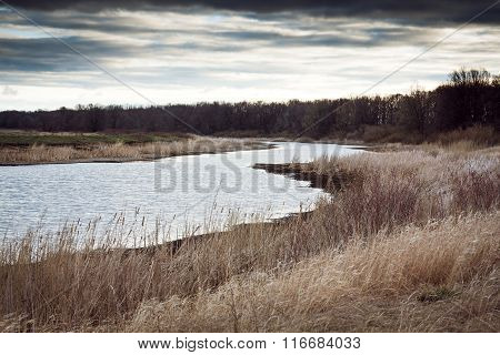 River curve at rural field during sunrise in overcast spring day