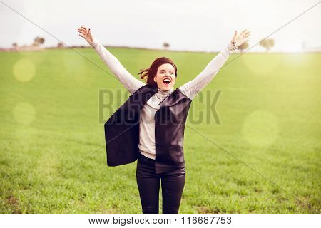Brunette woman jumping in the countryside.