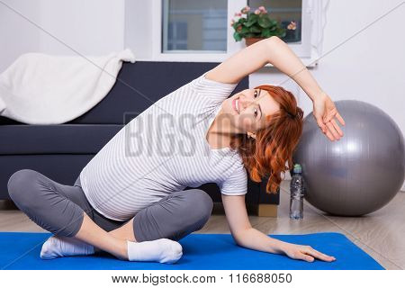 Pregnant Woman Doing Stretching Exercises At Home