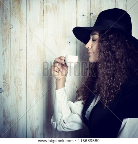 Vintage stylization of lady with cup of coffee smelling delicate aroma of beverage. Young attractive woman with rich long curly brown hair in retro dress and hat drinking coffee.