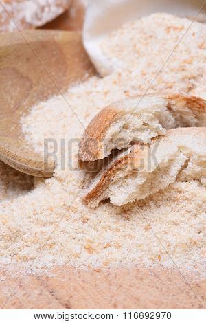 Bread crumbs on wooden table with spoon