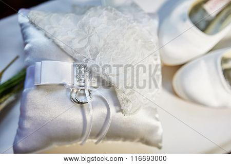 Wedding Rings On A Cushion, And The Bride's White Shoes
