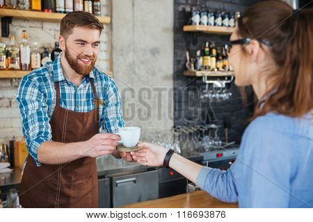 Handsome smiling barista with beard giving white cup of coffee on wooden coaster to young woman in glasses in cafe