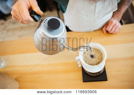 Closeup image of barista pouring water on coffee ground with filter