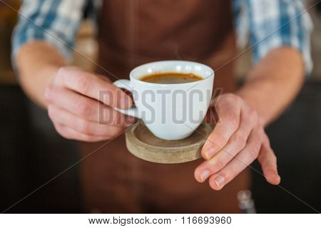 Closeup of white cup of coffee on wooden coaster holded by hands of barista in brown apron