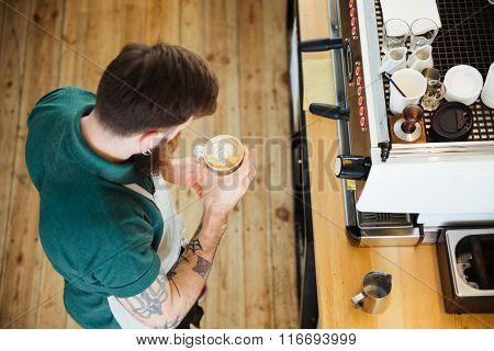 Top view portrait of barista preparing cappucino in coffee shop