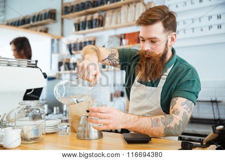 Barista pouring water in glass in coffee shop
