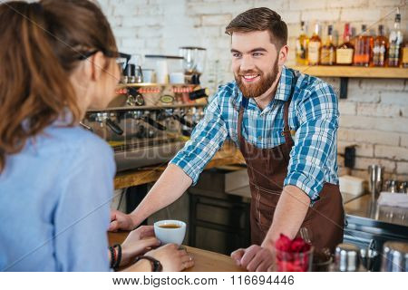 Cheerful bearded barista talking with young woman in coffee shop