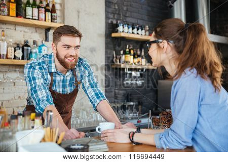 Smiling barista and young pretty woman in glasses talking in coffee shop
