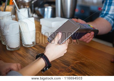 Woman paying for coffee by mobile phone and using reader holded by waiter in cafe