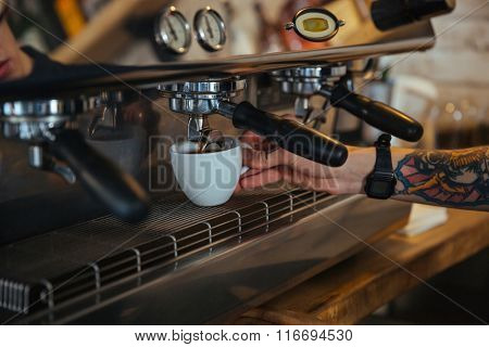 Coffee machine making coffee in white cup holded by tattooed barista hand