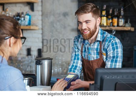 Young woman in glasses paying by credit card and entering pin code on reader holded by smiling bearded barista in cafe