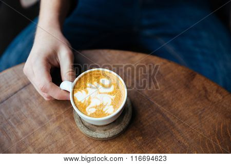 Top view of coffee with milk in white cup on wooden table holded by hand of man in jeans
