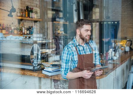 Handsome smiling bearded waiter in brown apron standing in cafeteria and holding tablet