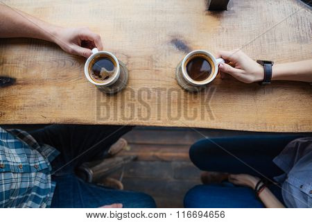 Top view of two cups on the table in cafe holded by hands of young couple