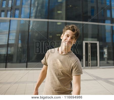 young man stand in front of modern business building, dreams come true hands up enjoying gesturing