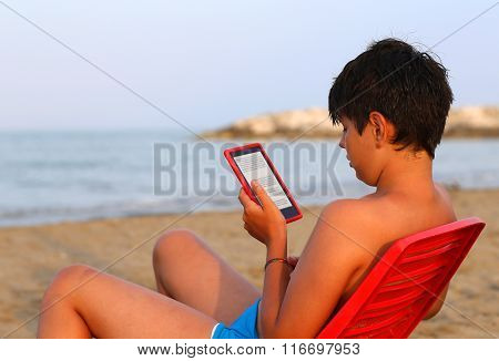 Caucasian Boy Reads An E-book