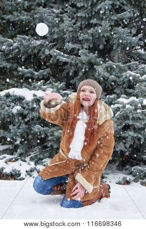 Girl play snowballs in winter forest at day. Snowy fir trees. Redhead woman full length.