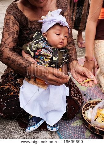 A Balinese baby boy is gifted with gold and silver jewelry during his Hindu baby-naming ceremony