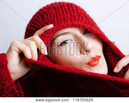 young pretty woman in sweater and scarf all over her face, winter cold close up coming, red lips mak