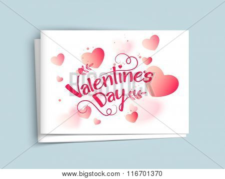 Glossy hearts decorated elegant greeting card with envelope for Happy Valentine's Day celebration.