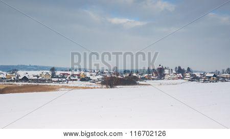 Winter Field Near Village Landscape Under Cloudy Sky.